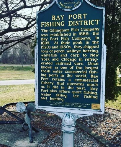 Interpretive sign: Bay Port Fishing District. The Gillingham Fish Company was established in 1886; the Bay Port Fish Company, in 1895. At their peak in the 1920s and 1930s, they shipped tons of perch, walleye, herring, whitefish and carp to New York and Chicago in refrigerated railroad cars. Once known as one of the largest fresh water commercial fishing ports in the world, Bay Port retains a commercial fishery that operates much as it did in the past. Bay Port also offers sport fishing, water skiing, ice fishing and hunting.
