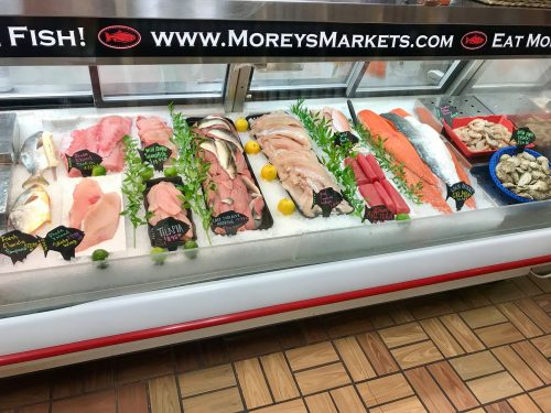 Grocery Store fish case with many varieties of fish on ice